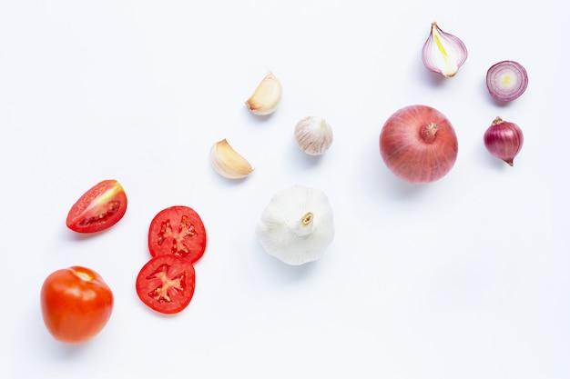 Frischgemüse auf weißem hintergrund. tomate, rote zwiebel, knoblauch,