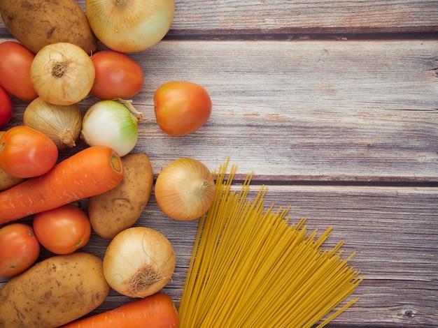 Frischgemüse, das eine mischung von spaghettis ist, briet die zwiebeln, die karotten, die kartoffeln, die tomaten, gesetzt auf einen alten holztisch. ansicht von oben