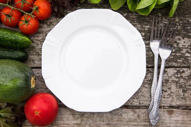 Frischgemüse für den geschmackvollen vegan- und diätkochen oder -salat, die um leere platte auf rustikalem hölzernem hintergrund machen