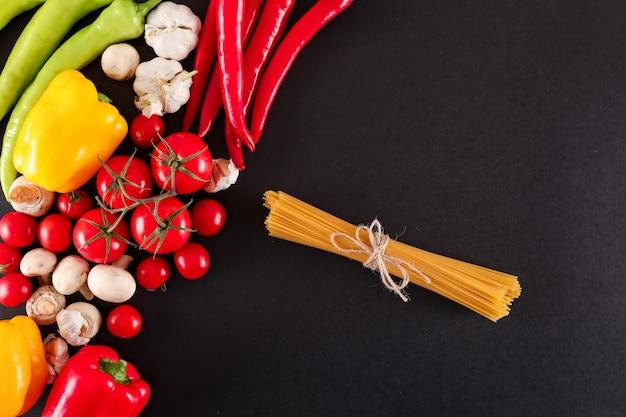 Frischgemüse und draufsicht der rohen spaghettis über schwarze oberfläche