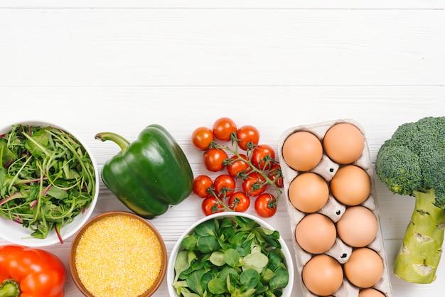Frischgemüse und eier auf weißem plankenbrett