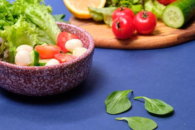 Frischgemüse und eine schüssel salat mit mozzarella auf einem blauen hintergrund. capresesalat . salat, kirschtomaten, mozzarella,
