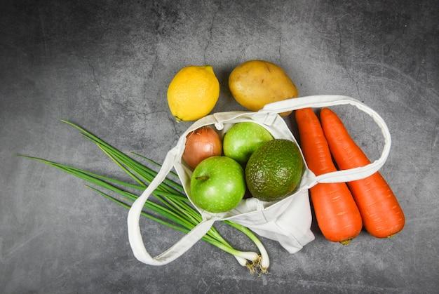 Frischgemüse und frucht organisch in den eco baumwollgewebetaschen auf tischdecken-segeltuch-stofftasche vom freien plastikeinkaufen des marktes - null abfallgebrauch weniger plastikkonzept