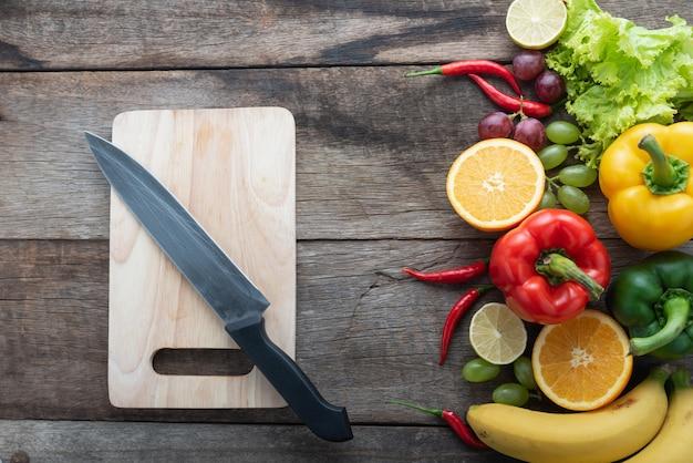 Frischgemüse und früchte für eignungsabendessen auf draufsicht des hölzernen hintergrundes