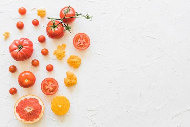 Frischgemüse und zitrusfrüchte auf weißem hintergrund