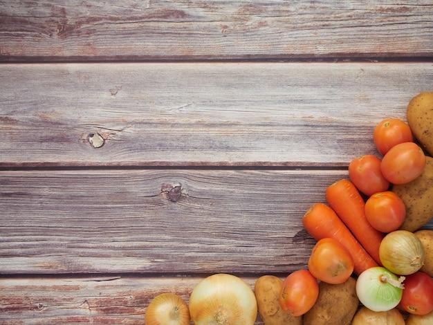 Frischgemüse, zwiebeln, tomaten, karotten, kartoffeln, gesetzt auf einen holztisch, draufsicht