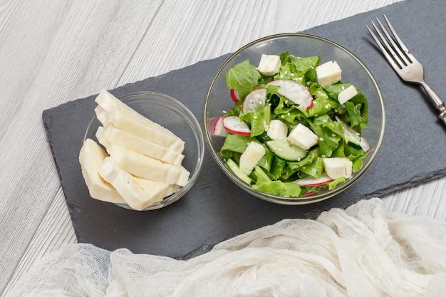 Frischgemüsesalat mit käse, gurke und rettich in der glasschüssel. alte metallgabel und glasschüsseln mit salat und käse auf steinbrett. ansicht von oben.