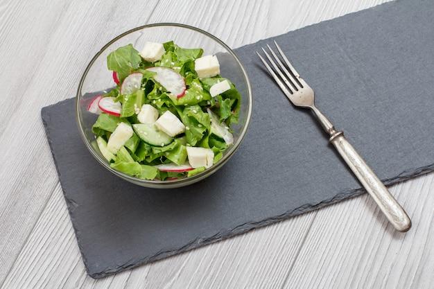 Frischgemüsesalat mit käse, gurke und rettich in glasschüssel, metallgabel auf steinbrett. ansicht von oben. Premium Fotos