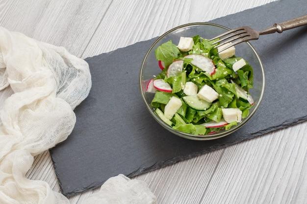 Frischgemüsesalat mit käse, gurke und rettich in glasschüssel, metallgabel und weißem tuch auf steinbrett. ansicht von oben.