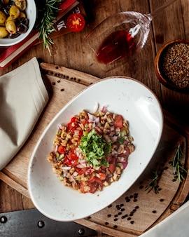 Frischgemüsesalat mit tomatenwürfeln, walnuss, roter zwiebel und kräutern