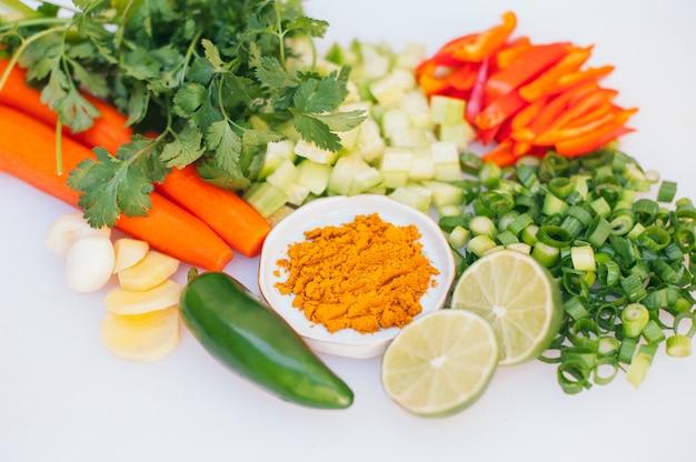 Frischgemüsezusammenstellung auf weißem hintergrund. grün, geschnittene limetten, pfeffer, karotten, gurken und limetten. gesundes ernährungskonzept. vegetarische produkte
