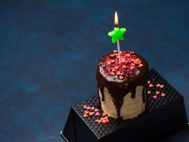 Frischkäse-biskuit mit schokoladenglasur und rosa herz besprüht auf dunkelblauem. geburtstagsfeier valentine muttertag behandeln