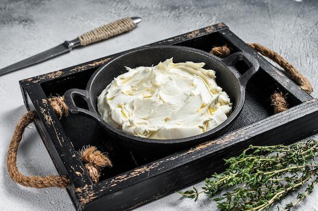 Frischkäse-mascarpone im holztablett für tiramisu. weißer hintergrund. ansicht von oben.