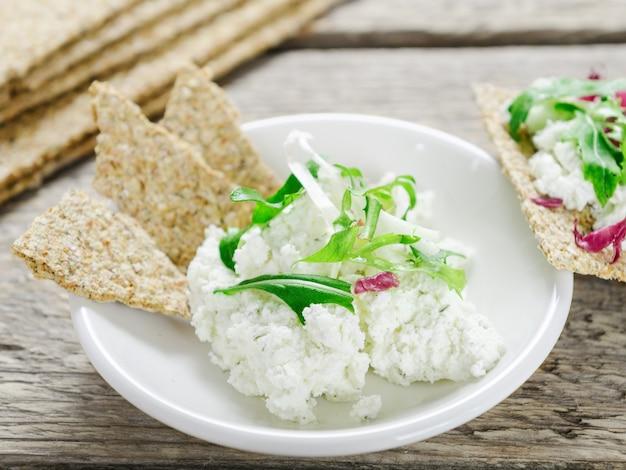 Frischkäse mit grüns und klarem brot auf einer weißen platte. gesundes essen.