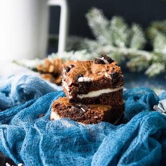 Frischkäseschokoladenkuchen mit plätzchen auf blau. quadratische schokoriegel der winterweihnachtsfestlichkeit.