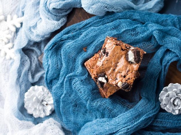 Frischkäseschokoladenkuchen mit plätzchen auf blau. winterweihnachtsfestlichkeitsquadrat-schokoriegel.