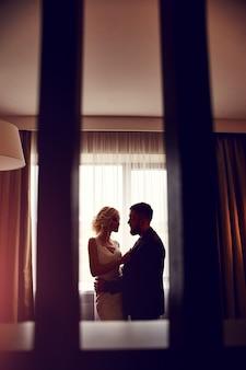 Frischvermählte am morgen im hotelzimmer sitzen auf dem bett, umarmen sich und schauen sich in erwartung der hochzeitszeremonie an. bärtiger hipster-bräutigam und blonde braut im langen hochzeitskleid