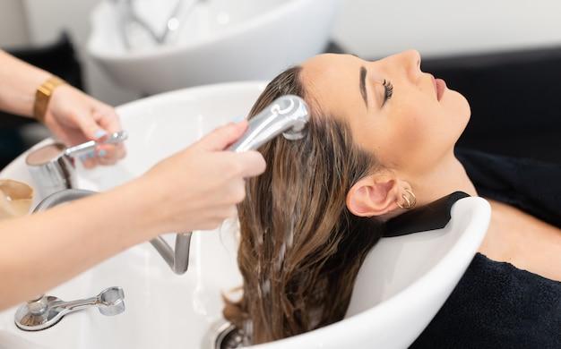Friseur bei der arbeit friseur, der der kundin blonde haare mit geschlossenen augen wäscht