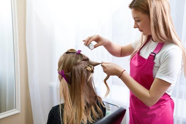 Friseur bringt puder für volumen auf das haar des kunden
