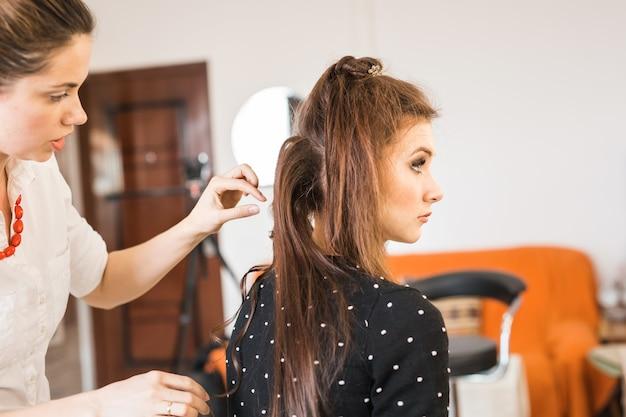 Friseur coiffeur macht frisur für junge frau