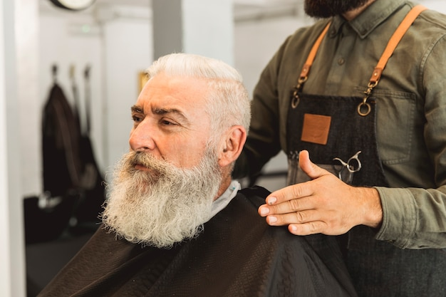 Friseur, der älteren kunden im friseursalon auswertet
