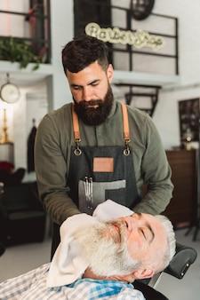 Friseur, der altes kundengesicht nach der rasur trocknet