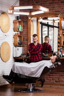 Friseur, der an eine frisur für kunden denkt