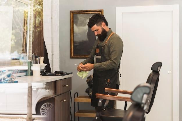 Friseur, der ausrüstung für arbeit im friseursalon vorbereitet