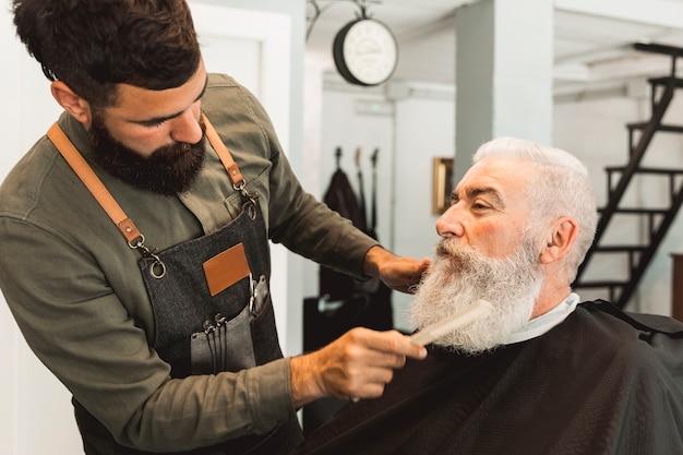 Friseur, der bart des gealterten kunden im friseursalon kämmt