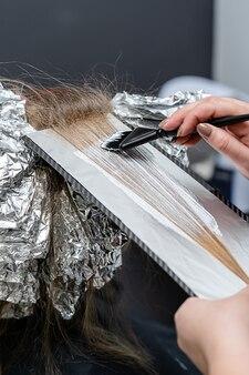 Friseur, der bleichpulver auf das haar des kunden aufträgt und in die folie einwickelt. shatush-technik