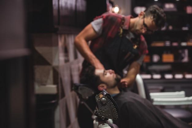 Friseur, der creme auf kundenbart aufträgt