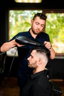 Friseur, der das haar seines kunden trocknet