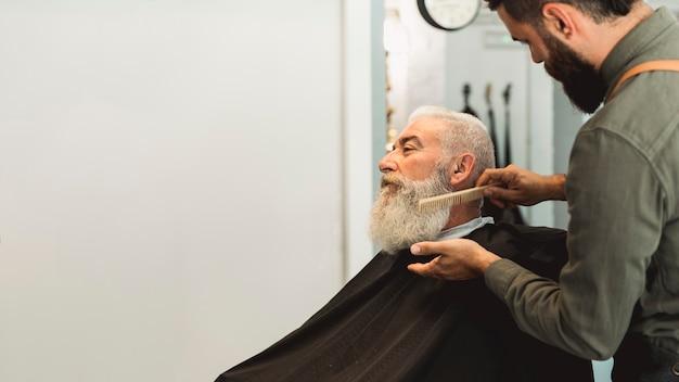 Friseur, der dem älteren kunden im salon bart kämmt