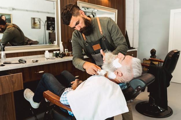 Friseur, der dem älteren kunden rasierschaum in schönheitssalon einsetzt