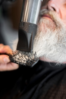 Friseur, der dem kunden bart im salon anreden lässt