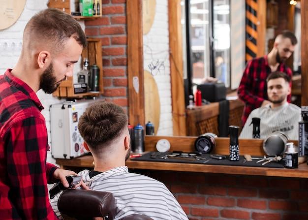 Friseur, der dem kunden den haarschnitt zeigt