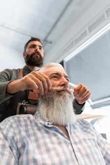 Friseur, der dem kunden im salon schnurrbart anredet