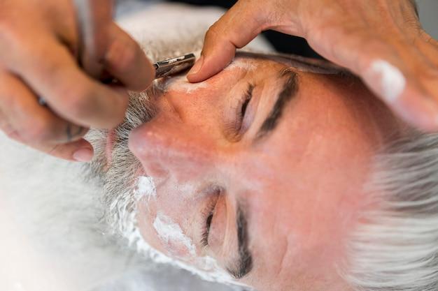 Friseur, der dem kunden im salon schnurrbart rasiert