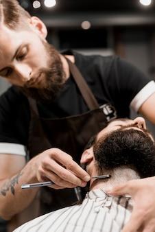 Friseur, der den bart des kunden mit rasiermesser rasiert