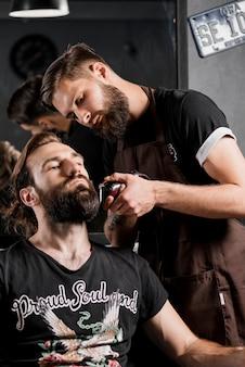 Friseur, der den bart des mannes mit elektrorasierer trimmt