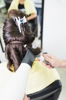 Friseur, der der jungen brunettefrau lockige frisur macht. selektiver fokus.