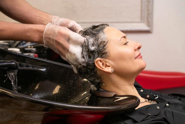 Friseur, der die haare einer frau wäscht