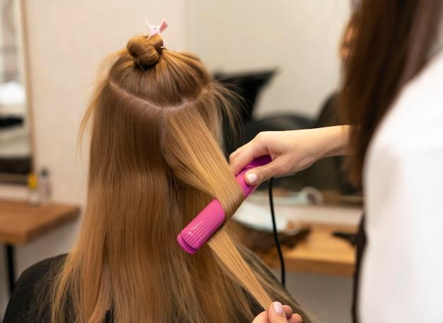 Friseur, der die haare eines kunden im salon stylt