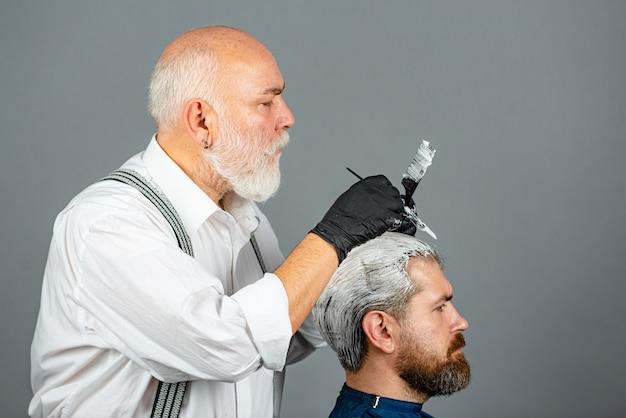 Friseur, der ein farbiges haar für einen bärtigen hipster-typ herstellt. professioneller friseur, der männerhaare färbt. prozess eines kerls, der haare beim friseur färbt. haare färben mann.