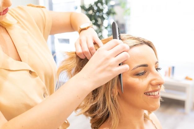 Friseur, der eine blonde frau in ihrer seitenansicht des friseursalons kämmt