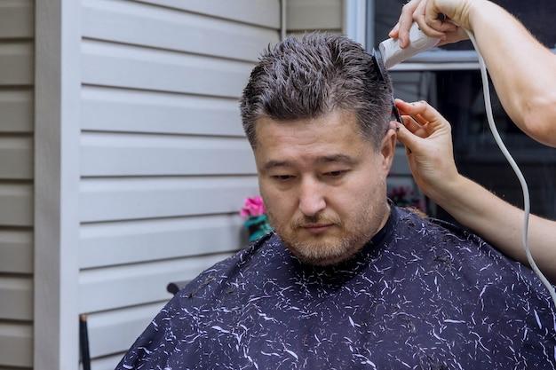 Friseur, der einem mann in einem haus die haare schneidet