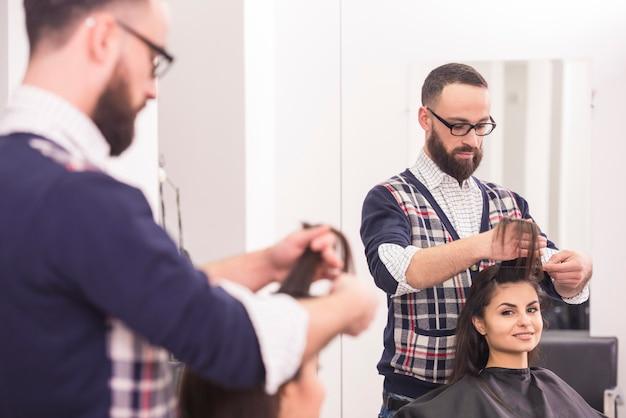 Friseur, der einen haarschnitt für ein schönes brunettemädchen macht.