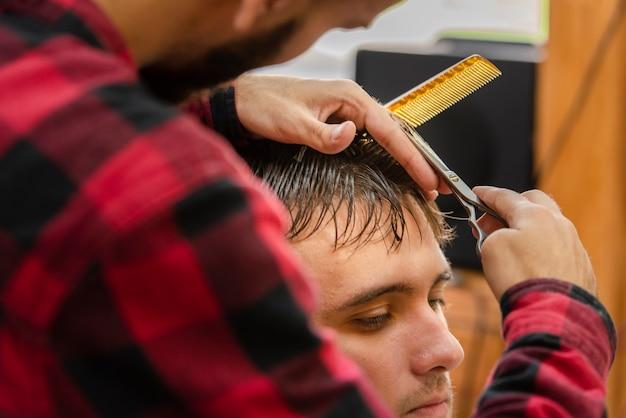 Friseur, der einen jungen mann mit einer schere trimmt