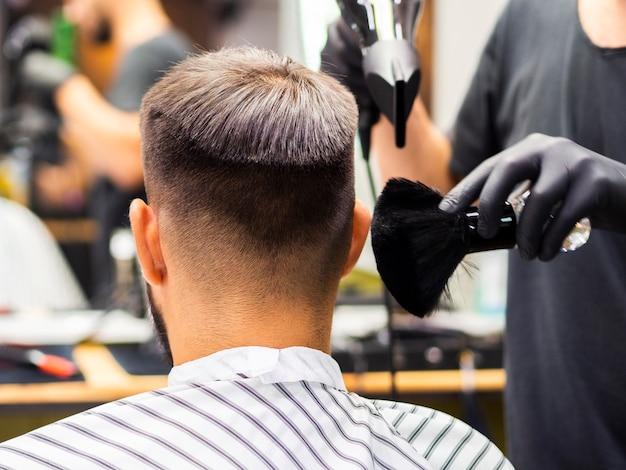 Friseur, der einen rasierpinsel und einen trockner verwendet