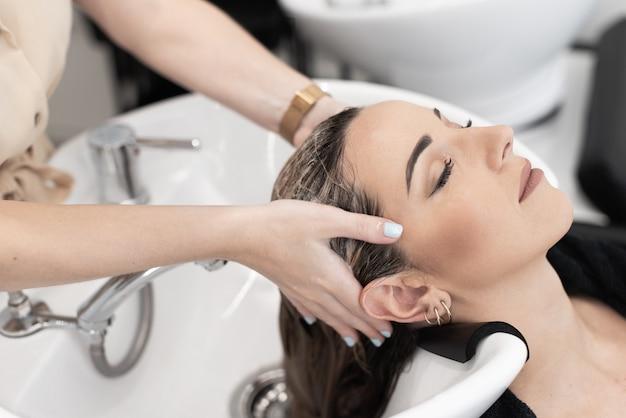 Friseur, der einer kaukasischen kundin mit geschlossenen augen eine kopfmassage gibt, während sie sie wäscht...